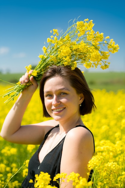 Девушка улыбается в желтом поле летом Premium Фотографии