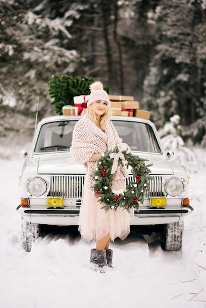 雪の森でレトロな車で覆われた手にクリスマスリースを持つ少女 Premium写真
