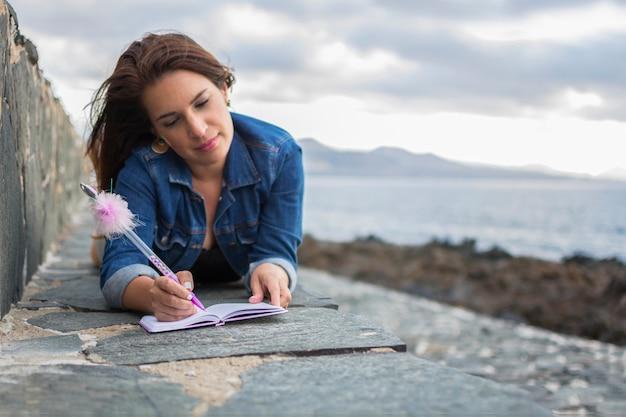 とても素敵なポンポンが付いているペンでピンクのノートに海の近くの屋外で書いている女の子。 Premium写真