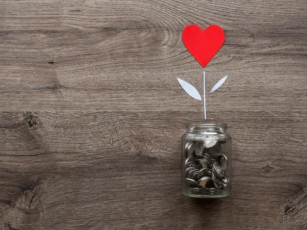 金属製のコインが入ったガラス缶と赤いハートの花が育ちます Premium写真