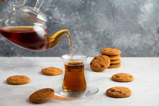 おいしいクッキーとお茶のガラスカップ。 無料写真