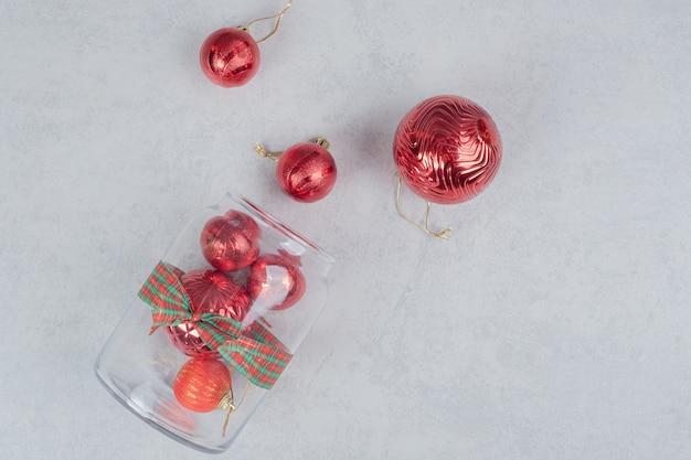 어두운 배경에 빨간색 크리스마스 볼의 유리 항아리. 무료 사진