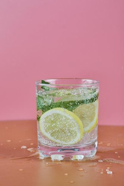 분홍색 표면에 차가운 상쾌한 레모네이드 한 잔 무료 사진