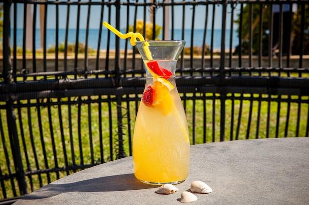 海とフルーツジュースのガラス。側面図。 無料写真