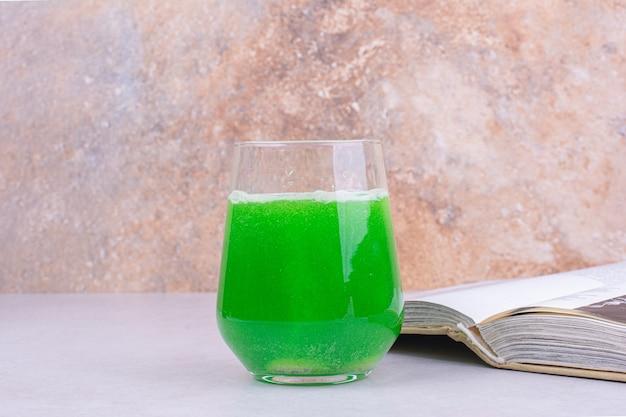 白いテーブルの上の緑のカクテルのグラス。 無料写真