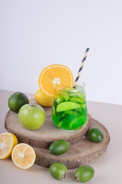 白い壁にフルーツスライスと新鮮な果物とジュースのガラス。 無料写真