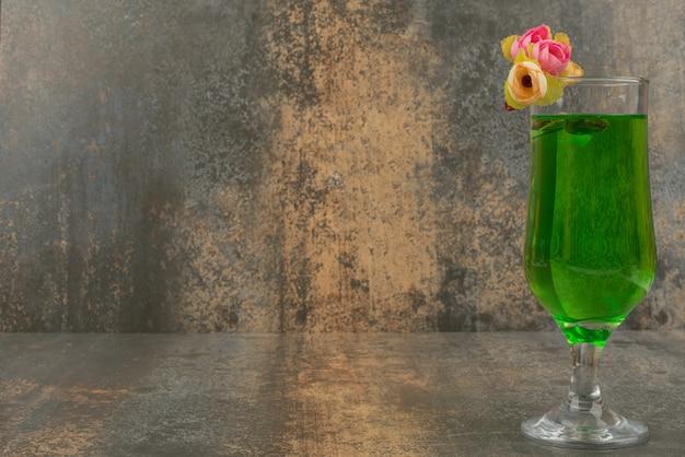 大理石の表面にジューシーなグリーンレモネードとバラのグラス。 無料写真