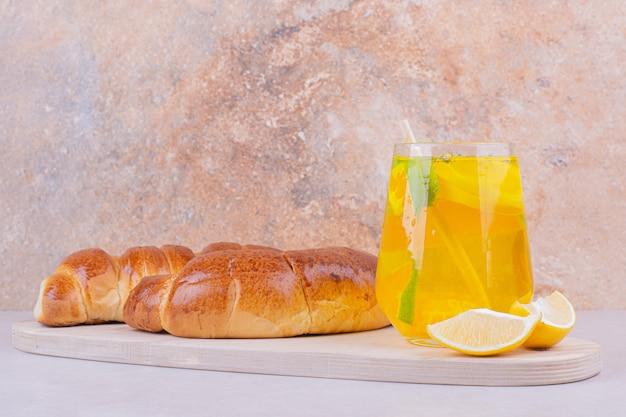 白い大皿に甘いパンとレモネードのグラス。 無料写真
