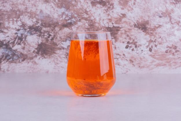 大理石の上のオレンジ色の飲み物のガラス。 無料写真