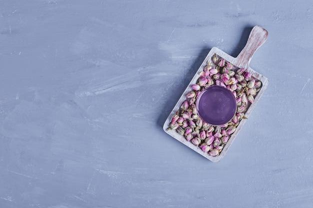 木製の大皿に花が咲く紫色の飲み物のグラス、上面図。 無料写真