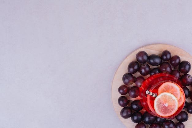 木の板に桜の果実と赤いジュースのガラス 無料写真