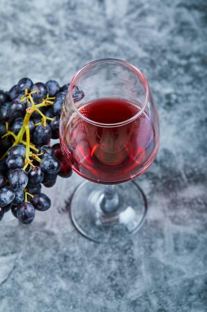 Бокал красного вина на мраморе с виноградом. Бесплатные Фотографии