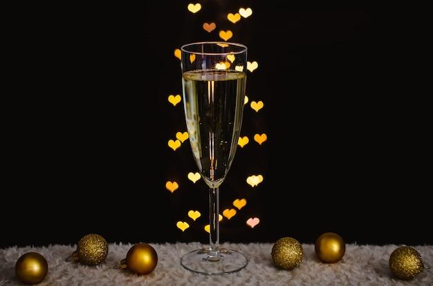 Бокал игристого вина с золотыми рождественскими украшениями с огнями боке в форме любви. Premium Фотографии