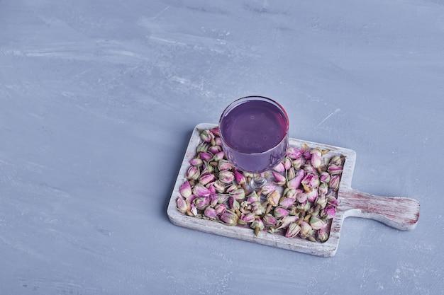 木製の大皿に花が咲くバイオレットジュースのグラス。 無料写真