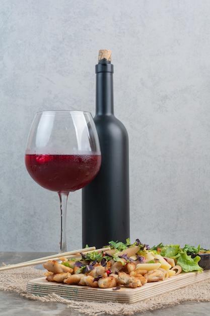 荒布にボトルとおいしいマカロニを添えたグラスワイン。 無料写真