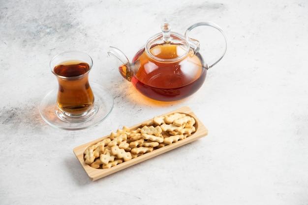 차 한잔과 크래커가 가득한 나무 판이있는 유리 주전자. 무료 사진