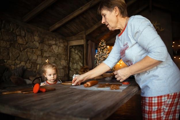 Бабушка и ее прекрасная белокурая внучка готовят печенье вместе в украшенном к рождеству доме Premium Фотографии