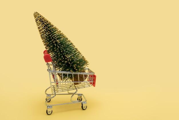 슈퍼마켓 장바구니에 녹색 크리스마스 트리입니다. 프리미엄 사진