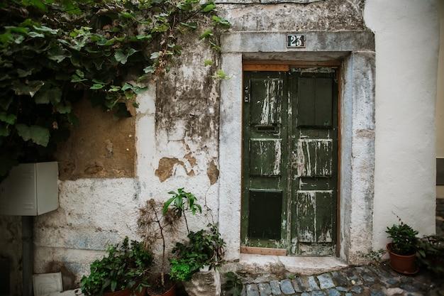 アルファマ地区の古い通りの1つにある緑の古いドア Premium写真