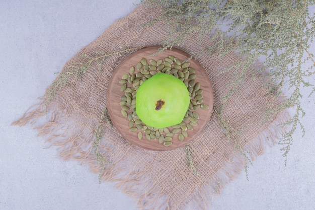 カボチャの種と木の板の上の緑の梨 無料写真