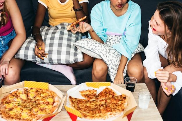 Группа различных женщин, сидящих на диване и едят пиццу вместе Premium Фотографии