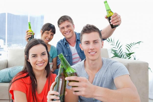 Группа друзей, празднующих звонкие бутылки вместе Premium Фотографии