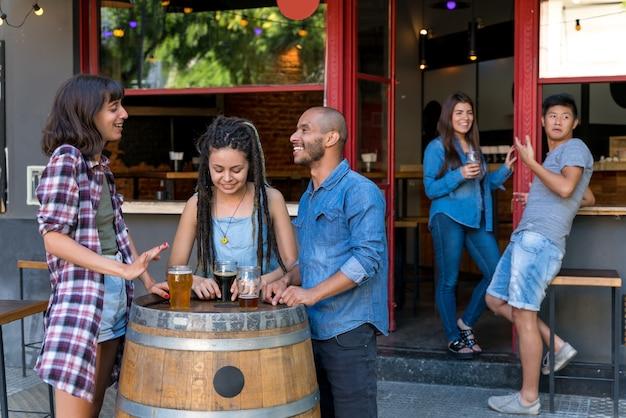 Группа друзей стоит у пивоваренной бочки, выпивая и весело болтая. Premium Фотографии