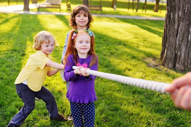 小さな幼児のグループが公園で綱引きをします。屋外ゲーム、子供時代、友情、リーダーシップ、子供の日。 Premium写真