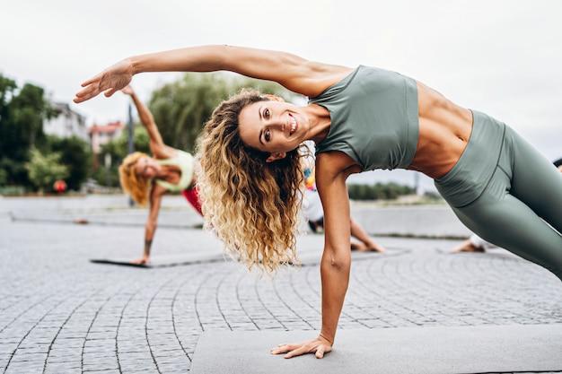 スポーティな女性のグループは、パーソナルコーチと一緒に公園のマットでヨガの練習をしています。アクティブなライフスタイル。 Premium写真
