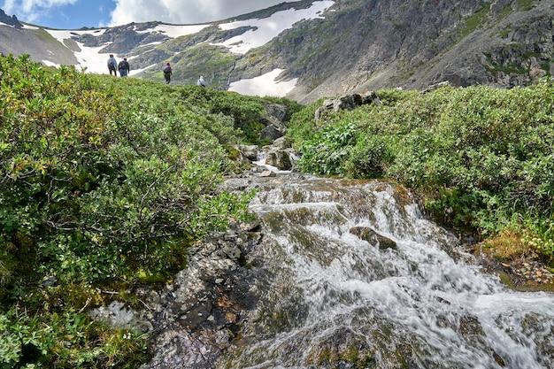 Группа туристов поднимается на вершину горы, проходя мимо горной реки. Premium Фотографии