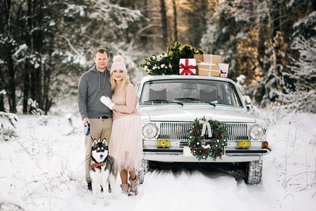 男と女がクリスマスの準備をして、ルーフツリーと冬の雪に覆われた森の中の贈り物の上でビンテージカーの背景の上に犬のハスキーを歩く Premium写真
