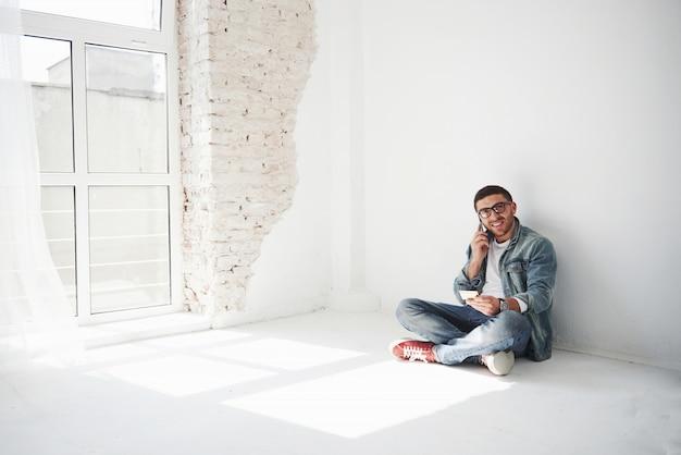 カジュアルな服を着た男が、クレジットカードを持って空のアパートに家に座って電話をかけています。 無料写真