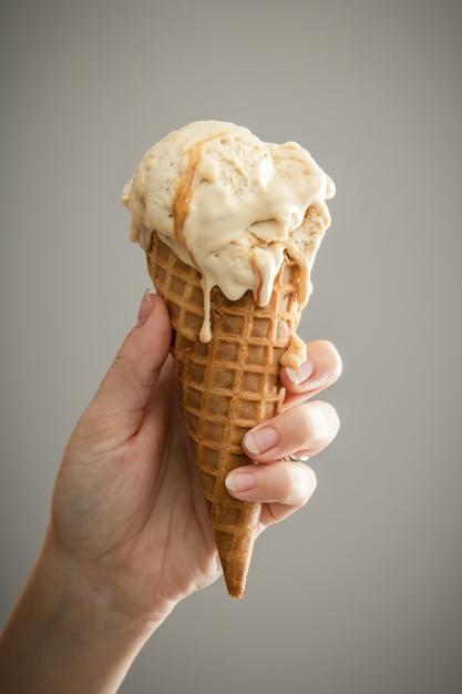 とろけるキャラメルのアイスクリームを持っている手 無料写真