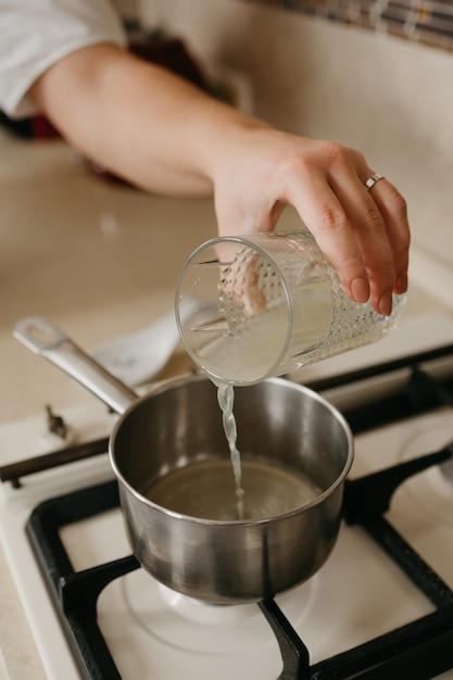 Рука женщины, которая наливает свежий лимонный сок из стакана в кастрюлю на газовой плите Premium Фотографии