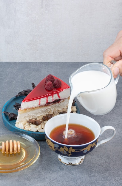 灰色のテーブルの上のコーヒーのカップに牛乳を注ぐ手。 無料写真