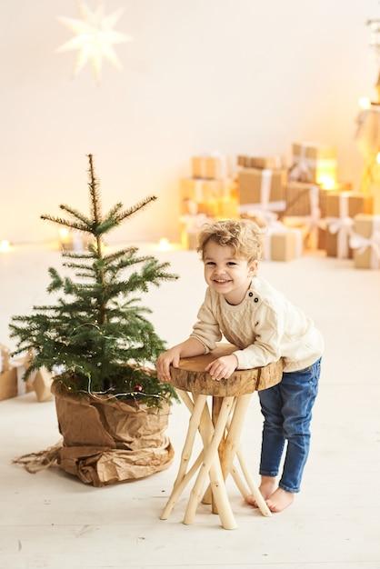 ハンサムな巻き毛の小さな男の子がクリスマスツリーの近くの木製の椅子に座っています Premium写真
