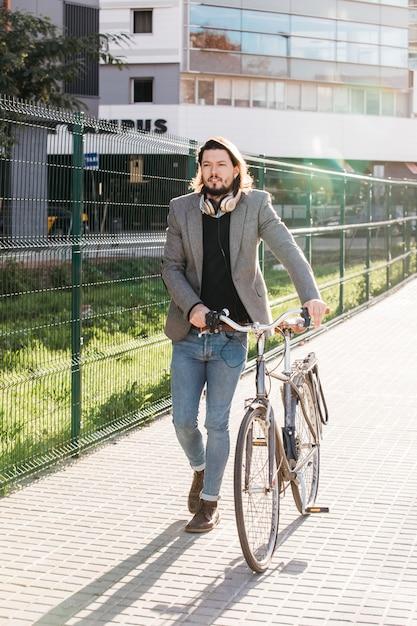 Красивый мужчина гуляет с велосипедом возле здания Бесплатные Фотографии