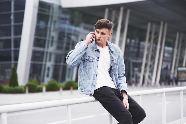 Красивый молодой человек разговаривает по телефону возле офиса. Бесплатные Фотографии