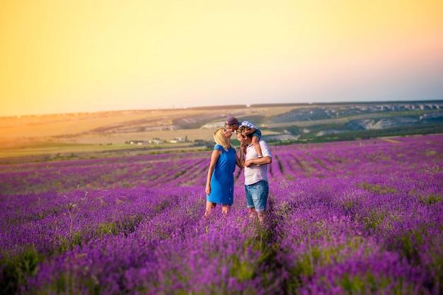 Счастливая семья с маленьким мальчиком гуляет и играет на прекрасном лавандовом поле. семейный отдых Premium Фотографии
