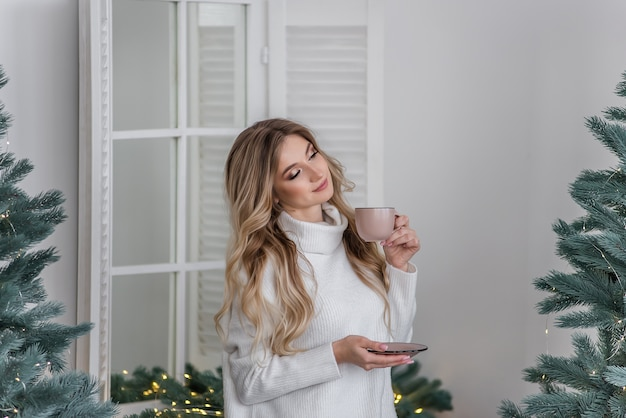 暖かい冬のセーターを着た幸せな女の子がスカンジナビアスタイルのキッチンに立って、クリスマスツリーのそばのピンクのカップから温かい飲み物を飲みます。新年の朝。お祝いのインテリアと家の装飾。 Premium写真