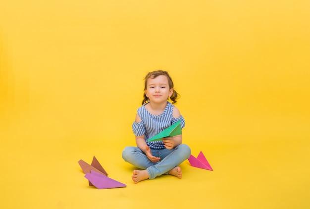 행복 한 여자는 노란색 종이 접기 종이 비행기와 함께 앉아 프리미엄 사진
