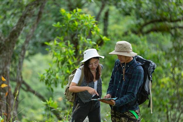 幸せなハイカーがバックパックでジャングルを歩きます。 無料写真