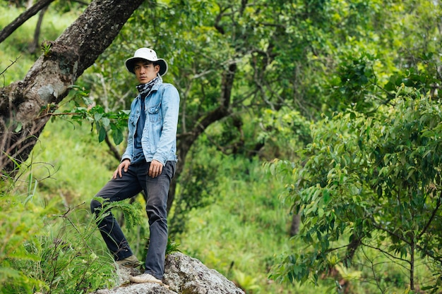 幸せなハイキング男がバックパックで森の中を歩きます。 無料写真