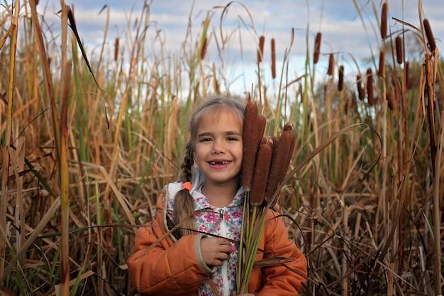 Счастливые дети веселятся в области рогоз, концепция экологии Premium Фотографии