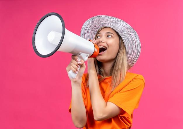 Счастливая симпатичная молодая женщина в оранжевой футболке в шляпе от солнца разговаривает через мегафон на розовой стене Бесплатные Фотографии