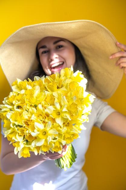 黄色い水仙の束と帽子をかぶった幸せな女性 Premium写真