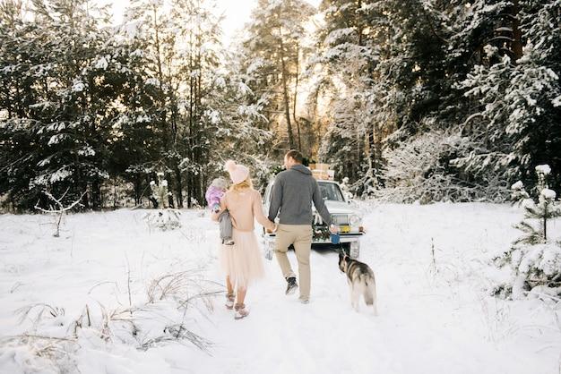 小さな子供を持つ幸せな若い家族は、レトロな車の背景にハスキー犬と一緒に、クリスマスツリーの屋根と雪に覆われた冬の森のプレゼントの上を歩いて、クリスマスの準備をしています。 Premium写真