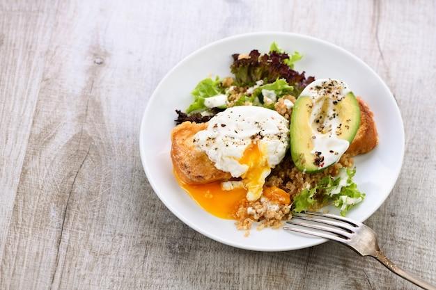 Здоровый и сбалансированный завтрак. яйцо бенедикта намазывается на тосты с половиной авокадо, киноа и салатом, приправленными специями и йогуртовой заправкой. Premium Фотографии