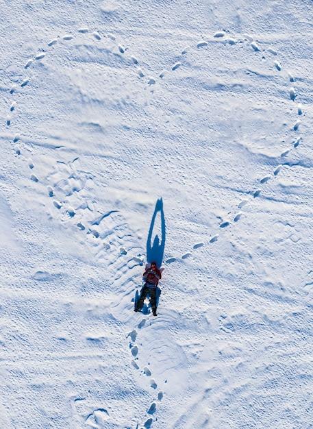 Сердце, нарисованное зимой в поле в снегу, снятое дроном сверху. день святого валентина. Premium Фотографии