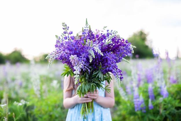 Хиппи девушка держит букет полевых цветов в ее руках. девушка спрятала лицо за букетом люпинов. маленькая девочка держит большой букет фиолетовых люпинов в цветущем поле. концепция природы. настоящее время Premium Фотографии